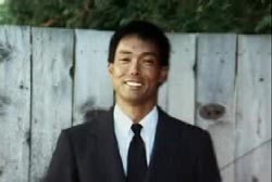 Smiling Eric Tamiyasu in a suit and tie