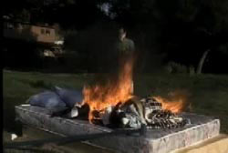 Mattress, sheets and pillows burning outside of a home