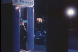 A man making a call at a phone booth