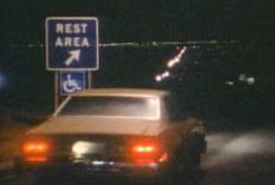 A car driving up to a rest area atop a hill late at night