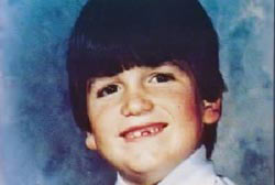 Smiling Gary Grant Jr.. He has a bowl haircut and is missing a front tooth