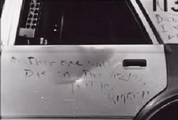 A cryptic message wtitten on the side door of a patrol car