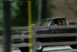 A man speeding down the road in a black pickup truck
