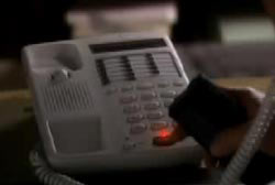 A person pressing buttons on a landline phone