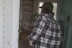 A man in a flannel shirt and hat walking into the Santos home