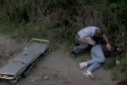 A crouching investigator examins the body of Jay Cook