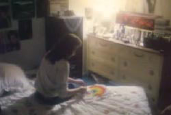 Kathy sitting on her bed in her bedroom writting something on a piece of paper