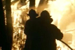 Two firefighters spraying down the Freeman home thats engulfed in flame