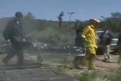 A fire fighter and EMT wheeling one of the Freemans to an ambulance