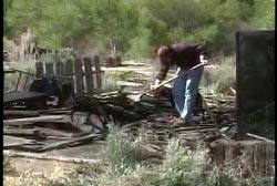 Jay Bible shoveling through the burnt remains of the house