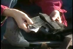 A kneeling person taking cash out of Lauria's purse
