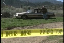 A man walking towards the yellow tape of a crime scene