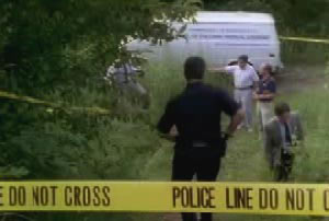 Police investigators entering a section of the woods that are walled off by yellow crime tape