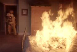 Firefighter entering a room that contains a bed engulfed in flames