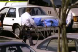 A police officer wheeling the covered body of Matt onto an ambulance