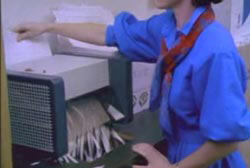 A woman puting Franke's papers through a paper shredder