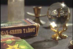 A table with a pack of tarrot cards and a crystal ball