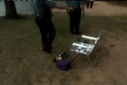 Police investigator's standing around an empty chair and small purple bag