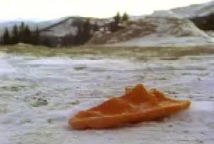 An orange sock in the middle of a snowy field
