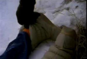 A man pulling down the boot of Annette to reveal an orange sock