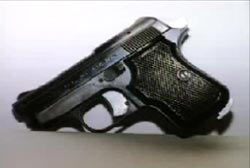 A tiny pistol placed against a white wall
