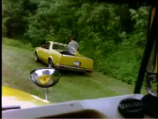 A man standing outside his bright yellow el camino on the side of a road
