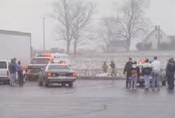Police officers and Ambulance arrive at the location of the body in a snowy field outside of a truck stop