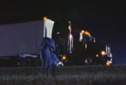 Man carrying a covered body into a field away from his semi-truck