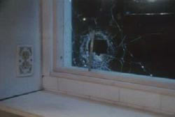 A window with a broken hole where a bullet flew threw