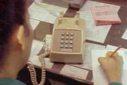 A woman writing notes on a note bad as she speaks over a landline phone