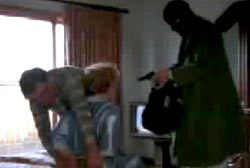 Roger ties up his wife with a rope as a gunman in a ski mask points his firearm at him