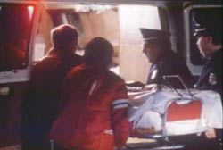 Police and EMT putting the covered body of Gryziec into the back of an ambulance