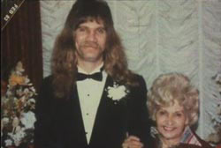 Terri with arm around son Tim McClure with a long mullet, mustache, and wearing a tuxedo