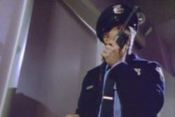 A security officer stading in a doorway radioing for other officers