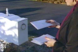 'Sean' putting letters into a white mailbox