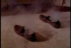 Shoes on carpeted floor with smoke coming out of them