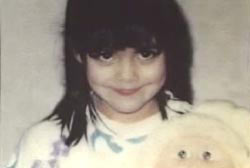 Smiling Alie Berrelez holding a stuffed toy