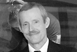 Bruce Ivins with a mustache in a suit and tie
