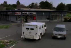 An armored are stopped in the parking lot of a gas station