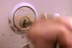 A hand shoving a key into a key hole