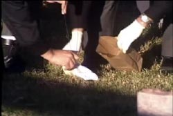 An investigator wearing latex gloves picking up a white sock