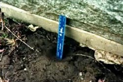 A blue ruler leaning against a gravestone