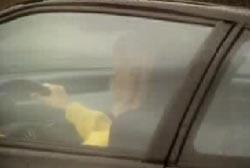 Woman in yellow shirt driving a car
