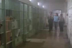 Handcuffed patty being escorted to her cell by two police officers