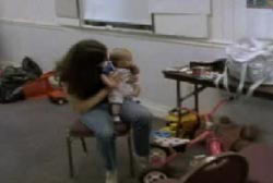 Patty holding a baby in her lap in what looks to be a classroom