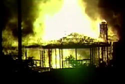 A large house on fire very badly engulfed in flames