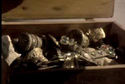 A treasure chest filled with golden goblets and swords