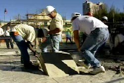 Construction workers lifting a small quare out of the ground at the Alamo