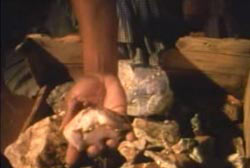 A hand grabing a piece of gold ore out of a wooden container