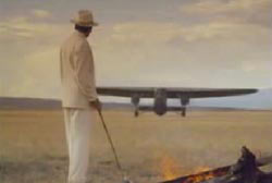 Leon Trabuco with a cane in a white suit and hat standing next to a campfire as a plane lands in the background